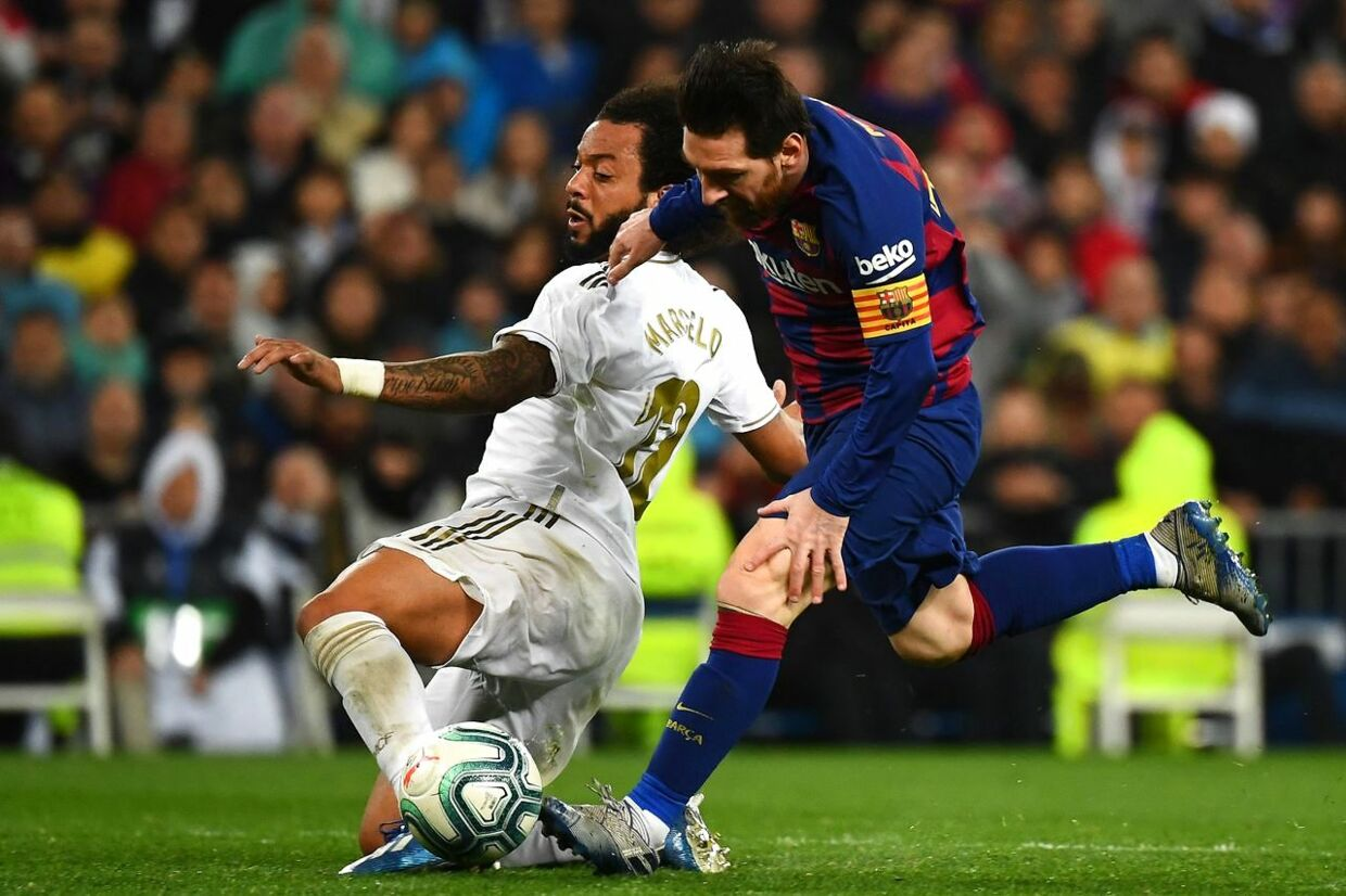 Barcelona's Argentine forward Lionel Messi (R) challenges Real Madrid's Brazilian defender Marcelo during the Spanish League football match between Real Madrid and Barcelona at the Santiago Bernabeu stadium in Madrid on March 1, 2020. (Photo by GABRIEL BOUYS / AFP)