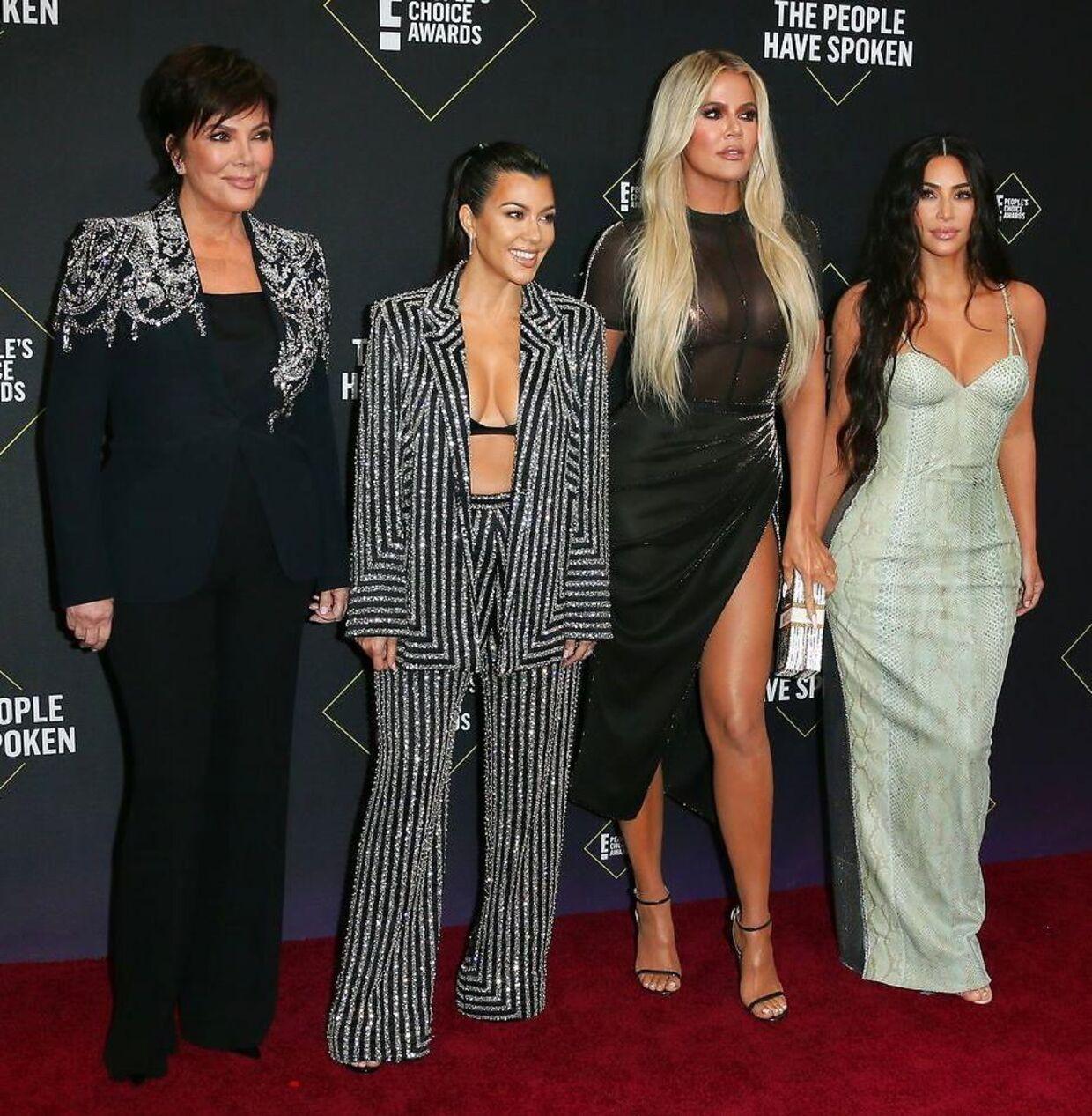 Kourtney Kardashian (i det stribede jakkesæt) med sin mor Kris Jenner og søstrene Khloé Kardashian og Kim Kardashian.
