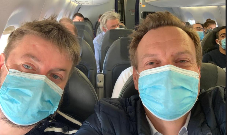 Rasmus Tantholdt sammen med sin kollega i et fyldt fly.