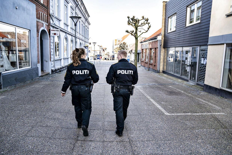 (ARKIVFOTO) Politi patruljerer i gågaden i Hobro, torsdag den 19. marts 2020. På turen i gågaden gik politiet ind i butikker for at sikre sig at der var de rigtige skilte med advarsler om corona i døren og håndsprit i butikken. Ritzau Scanpix.