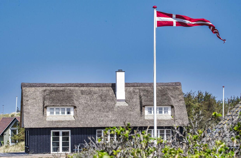 (ARKIV) Dannebrog vajer fra sommerhus. Danskerne er flittig bruger af sommerhusene, nu hvor grænserne er lukket for udenlandske turister. Vejers Strand turist område, den 23. maj 2020. Tyske, norske og islandske turister kan igen rejse til Danmark. Men kun uden for København. Mens de jubler på Vestkysten, ser det sort ud i Hovedstaden. Det skriver Ritzau, fredag den 29. maj 2020.. (Foto: John Randeris/Ritzau Scanpix)