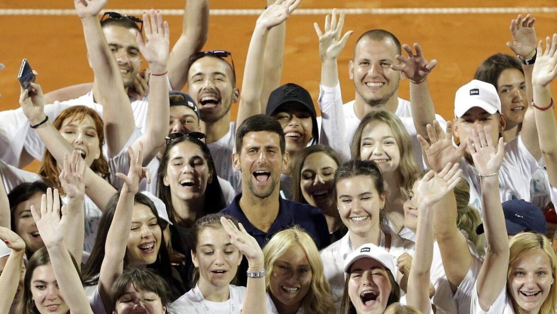 Novak Djokovic står her med nogle af turneringens frivillige. Han har tidligere været ret skarp i sin retorik om coronavirus.