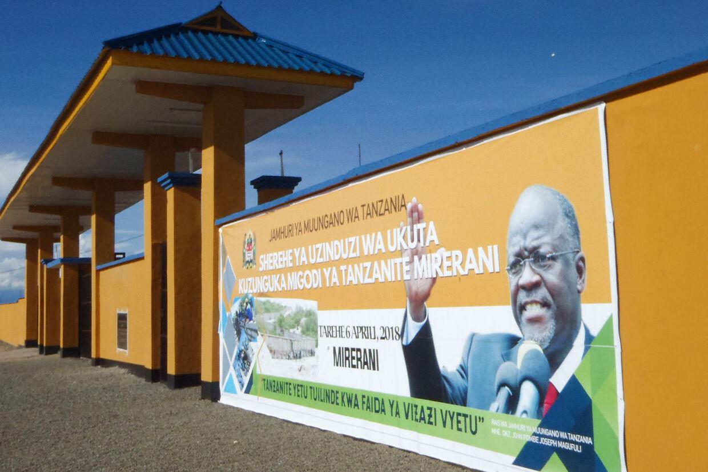 Et banner med præsident John Joseph Magufuli er sat op på væggen af det 24 km lange hegn omkring Melani, der skal stoppe smugleriet af Tanzanite.