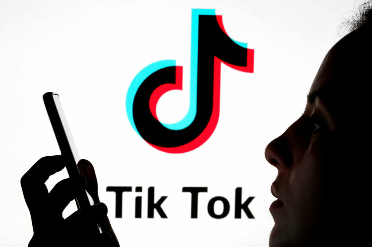 FILE PHOTO: A person holds a smartphone as Tik Tok logo is displayed behind in this picture illustration taken November 7, 2019. Picture taken November 7, 2019. REUTERS/Dado Ruvic/Illustration/File Photo