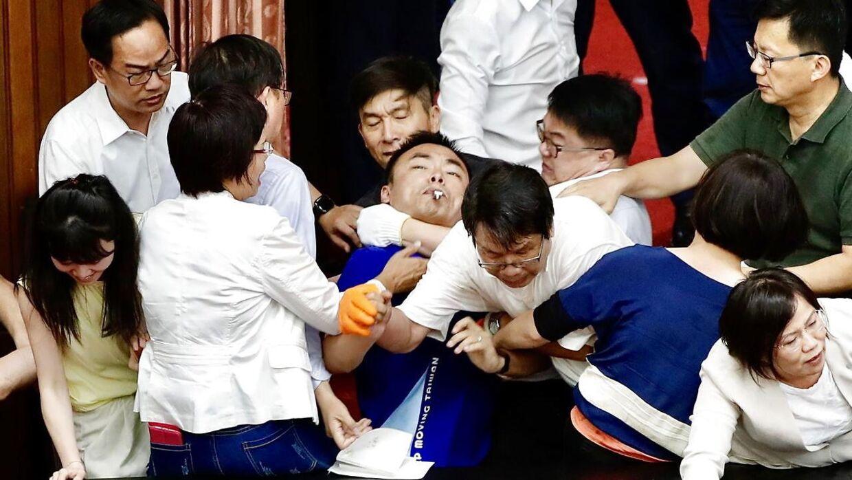 En slåskamp brød ud, da de regerende politikere brød barrikaden ned.