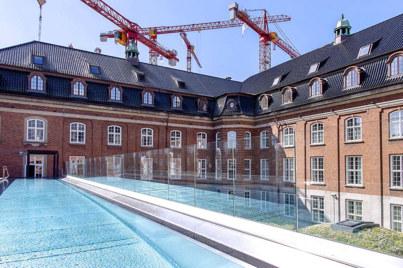 Udsigt mod den nyanlagte, sortglasserede tegltag på Villa Copenhagen. Kvistene og elevatortårnene er falset og inddækket med kobber. I forgrunden ses en 25 meter lange, udendørs pool, som bliver opvarmet med genbrugsvarme fra hotellet.
