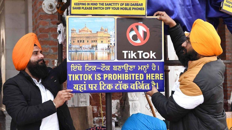 To sikher ved det Gyldne Tempel i Amritsar i det nordlige Indien hænger et skilt op, hvor det fremgår, at TikTok ikke må benyttes på stedet.