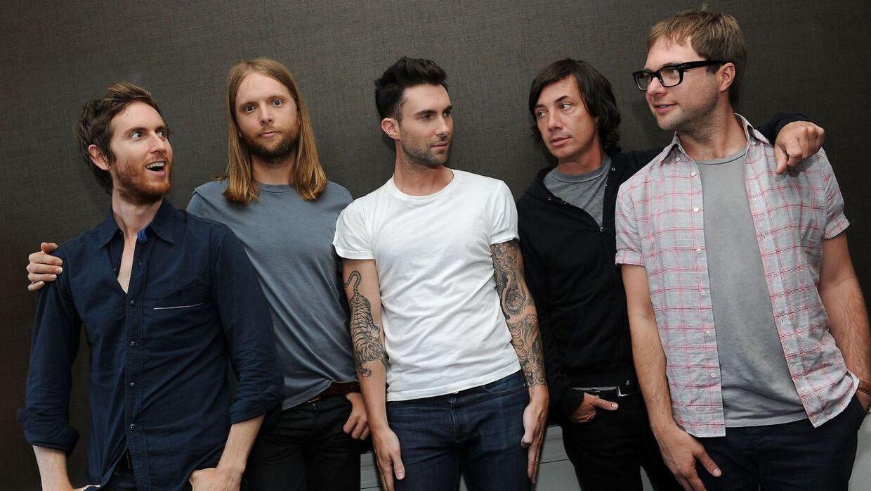 Maroon 5 med forsanger Adam Levine i midten. Til højre står Michael Madden.