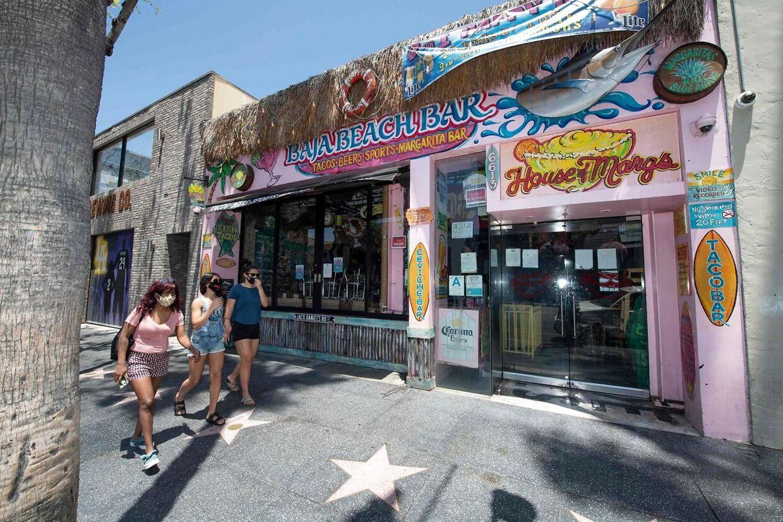 Tre kvinder, der alle bærer ansigtmaske, går forbi en bar, der er lukket igen i Los Angeles.