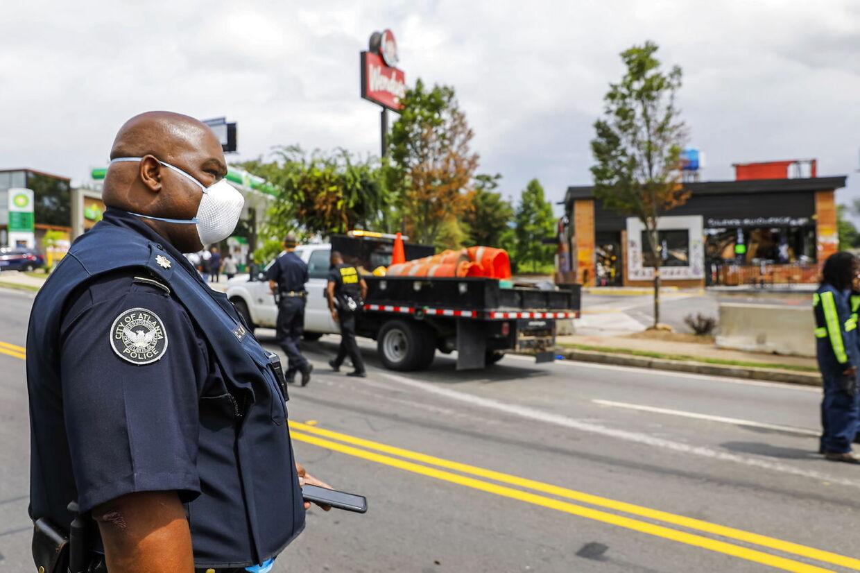En betjent fra Atlanta står foran restauranten, der efter en farvet mands død er blevet et center for demonstrationer, og senest drabet på den otteårige Secoriea Turner.