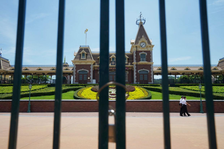 Mænd med ansigtsmasker går bag denne lukkede port i Hong Hong Disneyland.