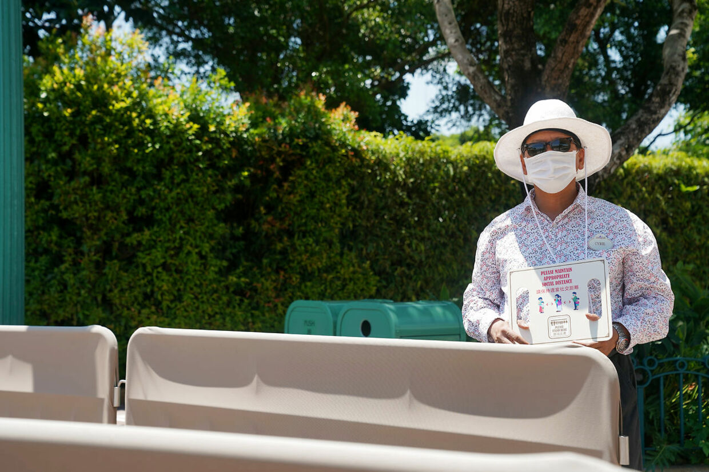 Et medlem af staben holder et skilt, der viser, at man skal holde social afstand i Hong Kong Disneyland.