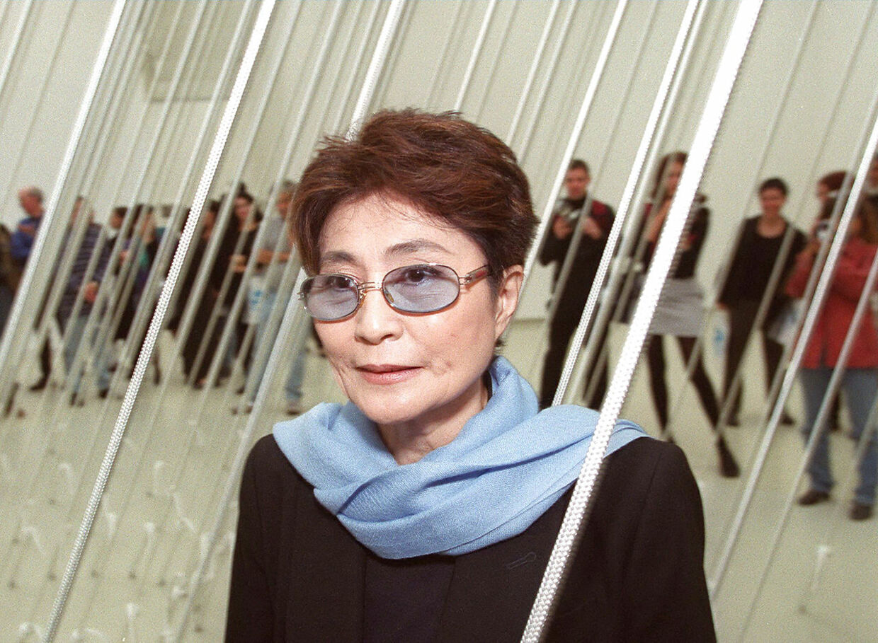 "Artist Yoko Ono, widow of the late John Lennon, poses in front of one of her artworks from a retrospective show at the Israeli Museum in Jerusalem 25 November 1999. The exhibition, titled ""Yoko Ono: Have You Seen the Horizon Lately"", will be inaugurated November 26 to promote Ono's efforts to advance world peace and unity. Ono, 66, will also open another exhibition in Um el-Fahm, an Arab town in central Israel."