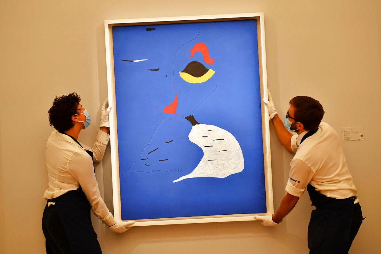 To assistenter er ved at hænge Joan Mirós maleri 'Maleri (Kvinde i rød hat)' op i London.