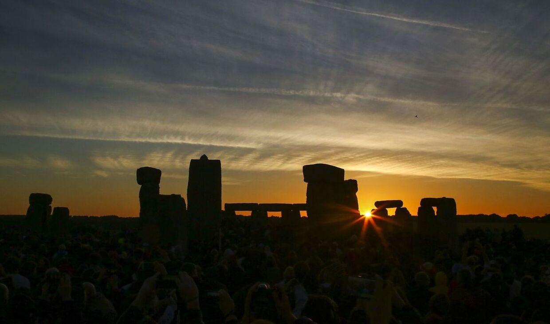 Sommersolen står op over Stonehenge.