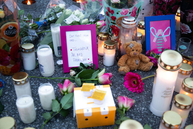 Blomster og lys på parkeringspladsen, hvor en 12-årig pige blev dræbt af skud.