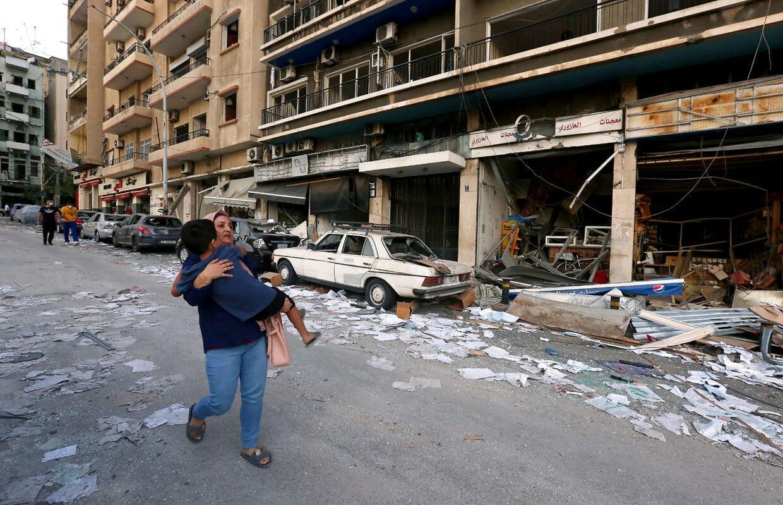 En kvinde løber med sin barn i armene. Væk fra ødelæggelserne fra eksplosionen i Beirut. REUTERS/Aziz Taher.