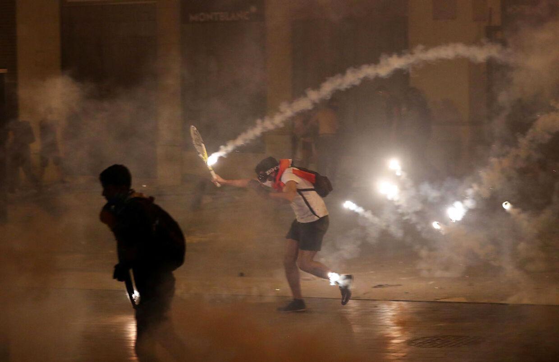 Flere demonstranter bruger tennisketsjere til at undvige det, der bliver kastet både af deres egne og politiet.
