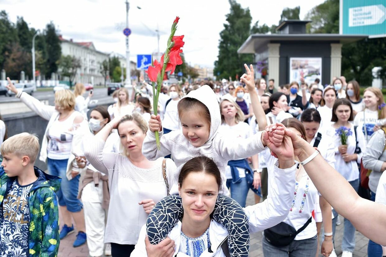 Hvidklædte kvinder og børn i protest mod politivold. Foto: Sergei GAPON / AFP)