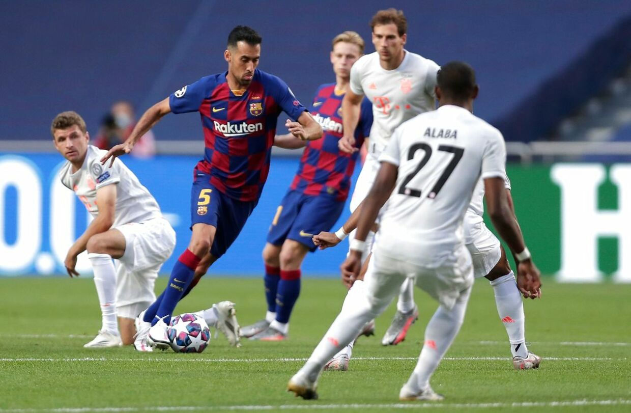Barcelona's Spanish midfielder Sergio Busquets (C) runs with the ball past Bayern Munich's German forward Thomas Mueller (L) during the UEFA Champions League quarter-final football match between Barcelona and Bayern Munich at the Luz stadium in Lisbon on August 14, 2020. (Photo by Manu Fernandez / POOL / AFP)