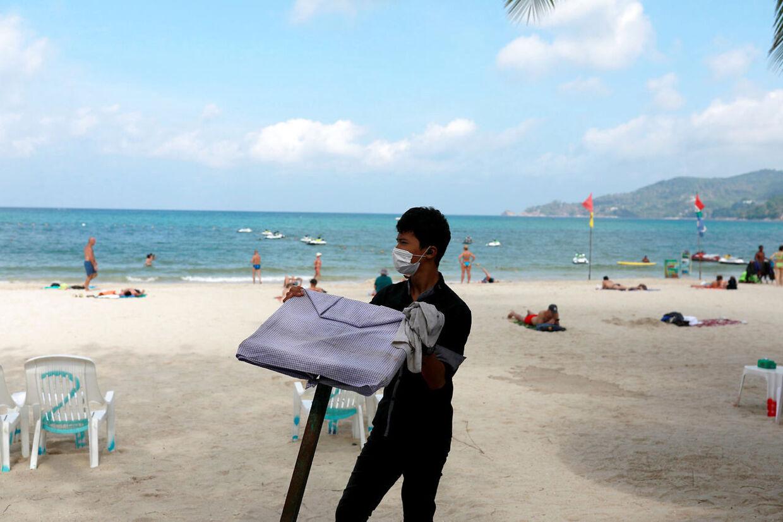 En tjener arbejder på stranden i Phuket i begyndelsen af marts, hvor der stadig var turister i landet. Reuters.