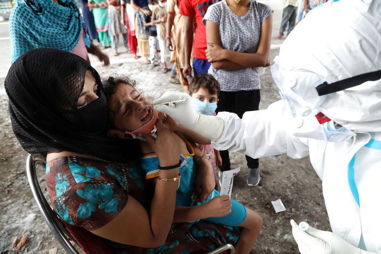 En sundhedsmedarbejder tager en corona-prøve fra et barn i Jammu, Indien, 25. august. 2020. EPA.