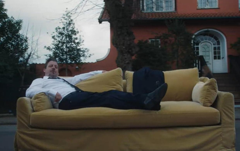 Anders W. Berthelsen ligger blandt andet i en sofa i kampagnevideoen. Billede: Kræftens Bekæmpelse.