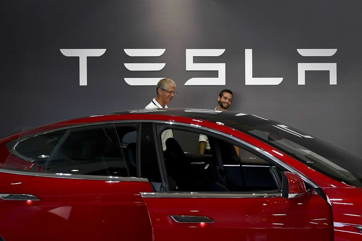 Two man stand in front of a Tesla logo behind the Tesla Model S at the electric carmaker Tesla showroom of El Corte Ingles store in Lisbon, on September 1, 2017. / AFP PHOTO / PATRICIA DE MELO MOREIRA