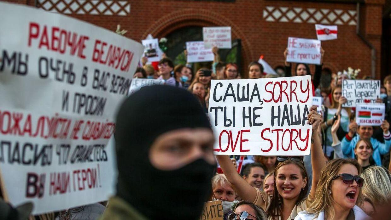En maskeret mand foran kvindelige demonstranter i Hviderusland.