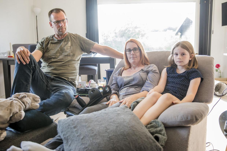 Gigtpatienten Tina Jensen på 46 år siddende på særlig liggesofa med sin mand, Henrik Jensen på 50 år, og sin datter, Emma på ni år. Foto: Nikolai Linares/Byrd.