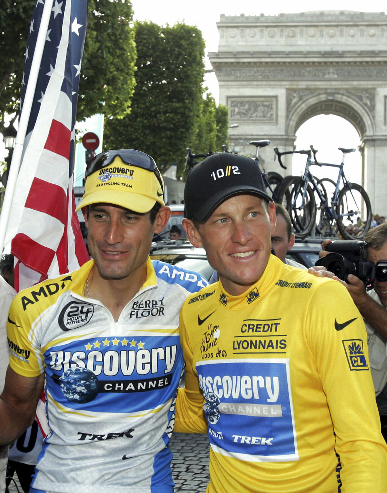 Discovery Channel team rider Lance Armstrong of the U.S. (R) and team mate George Hincapie pose for supporters in Paris after Armstrong won his seventh straight Tour de France, July 24, 2005. George Hincapie, one of Lance Armstrong's former team mates and closest allies, has admitted to using performance-enhancing drugs. The 39-year-old American, who rode alongside Armstrong in each of his seven Tour de France wins, released a statement on Wednesday confessing that he cheated. Picture taken July 24, 2005. REUTERS/Philippe Wojazer/Files (FRANCE - Tags: SPORT CYCLING DRUGS SOCIETY)