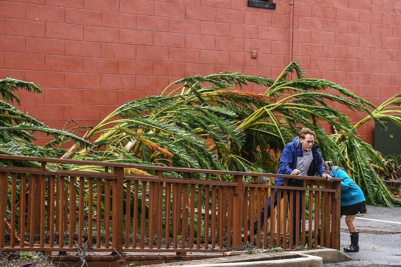 Et par må klynge sig til rækværket i det voldsomme blæsevejr i byen Pensacola, Florida.