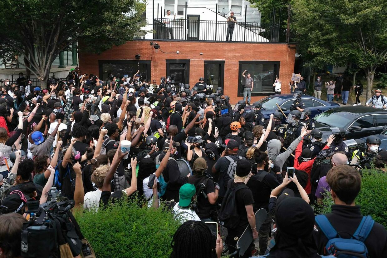 Kampklædt politi danner en mur foran demonstranterne,