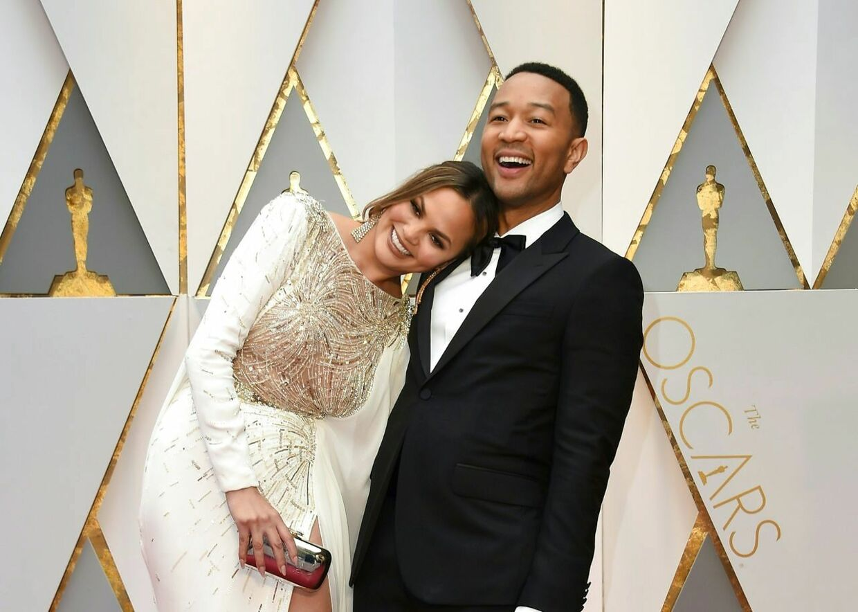 TOPSHOT - John Legend (R) and US model and wife of John Legend Chrissy Teigen arrive on the red carpet for the 89th Oscars on February 26, 2017 in Hollywood, California. / AFP PHOTO / VALERIE MACON
