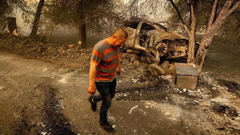 En knust Osvaldo Ramirez på vej væk fra sin bil, som blev offer for flammerne. I den var en stor sum penge og familiens id-papirer.