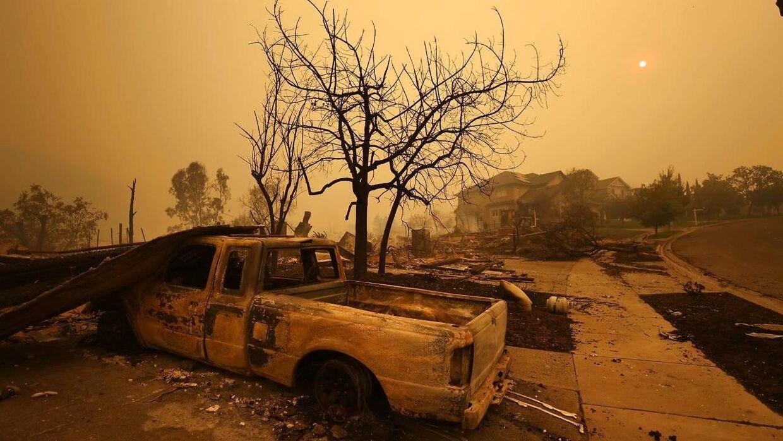 En udbrændt bil i Napa, hvor et gulligt lys dækker for dagssolen.