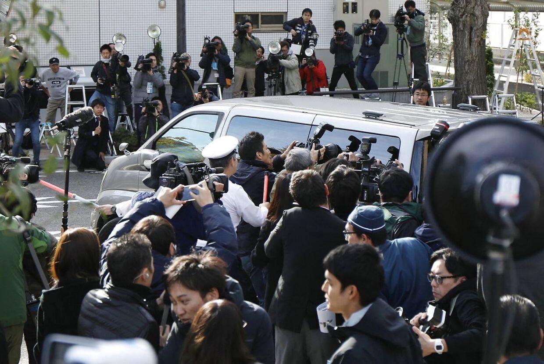 Fotografer omringer en bil, der transporterer Takahiro Shiraishi, efter et besøg hos anklagemyndigheden.