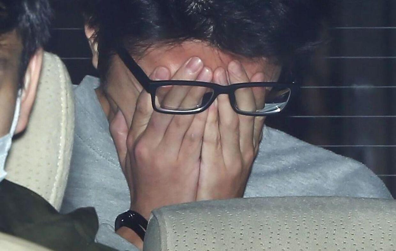 Takahiro Shiraishi gemmer sit ansigt, mens han er på vej til anklagerens kontor.