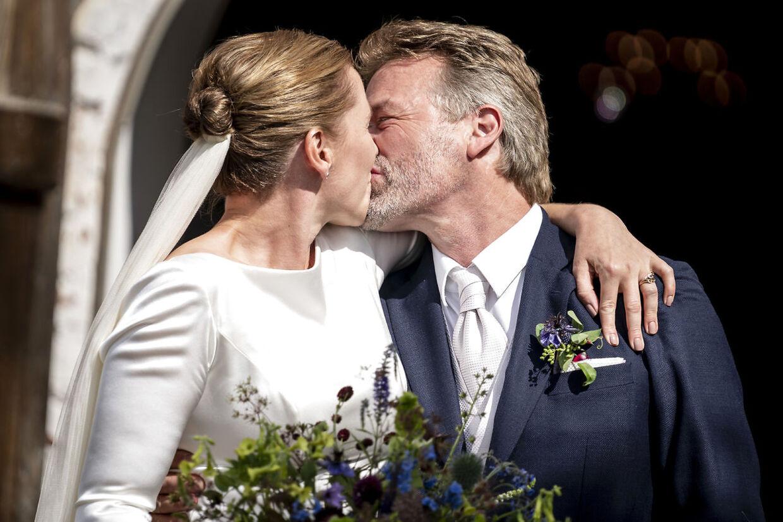 Mette Frederiksen og Bo Tengberg kysser foran Magleby Kirke, efter at de er blevet gift.