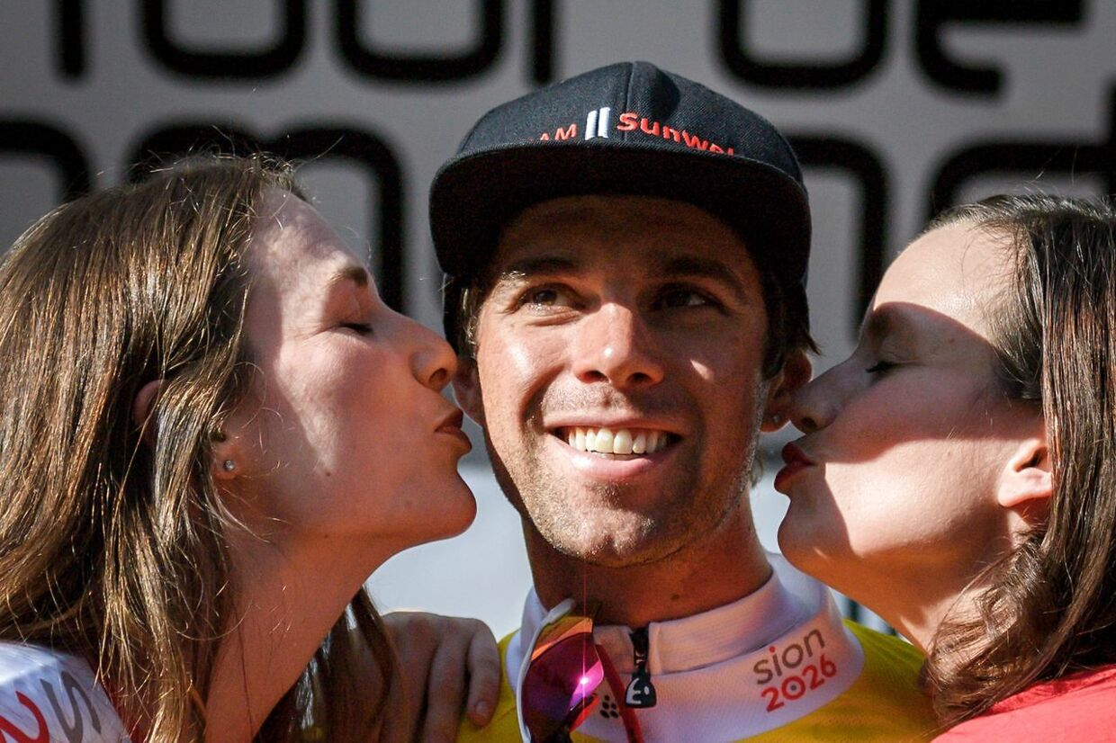 Australia's Michael Matthews of Team Sunweb (C) is kissed by hostesses after winning the prologue, a 4km race against the clock, Fribourg to Fribourg, at the Tour de Romandie UCI Pro cycling race in Fribourg on April 24, 2018 / AFP PHOTO / Fabrice COFFRINI