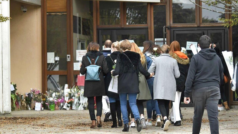Et samfund i chok: Forældre og børn lægger blomster foran skolen i Conflans-Sainte-Honorine.