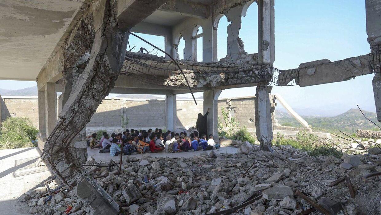 En lærer på Al-Wehdah-skolen i Yemen bruger en ødelagt betonvæg som tavle. Klasseværelset er omringet af murbrokker.