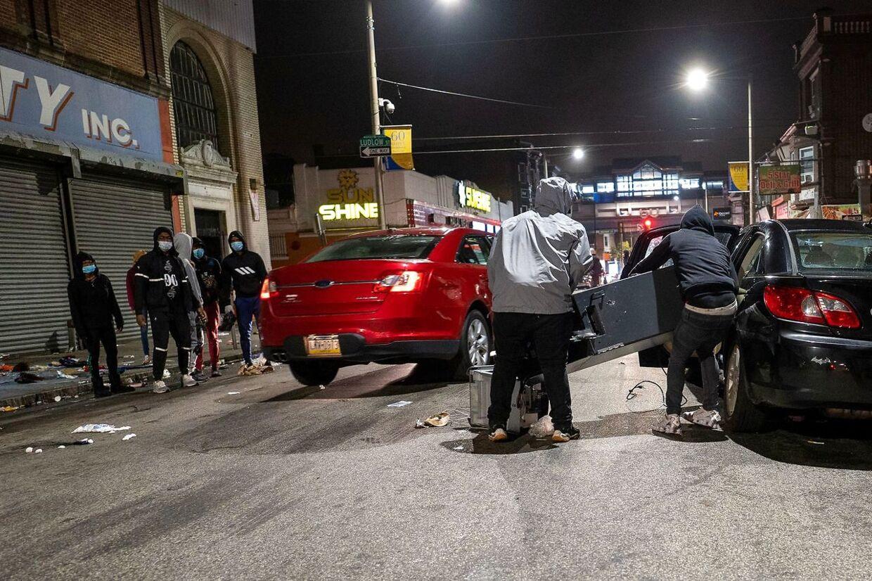 Demonstranter læsser en stjålet hæveautomat ind i en bil.