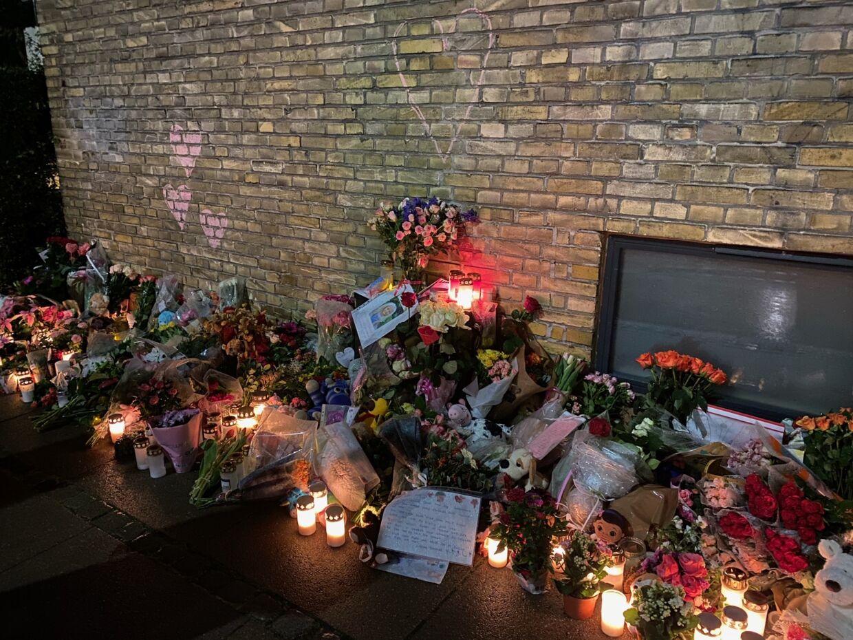 Der er tegnet røde kridthjerter på væggen. På fortovet står blomster, bamser og levende lys.