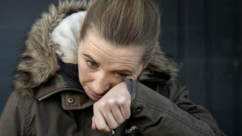 Statsminister Mette Frederiksen tører hun en tåre væk fra sin kind.