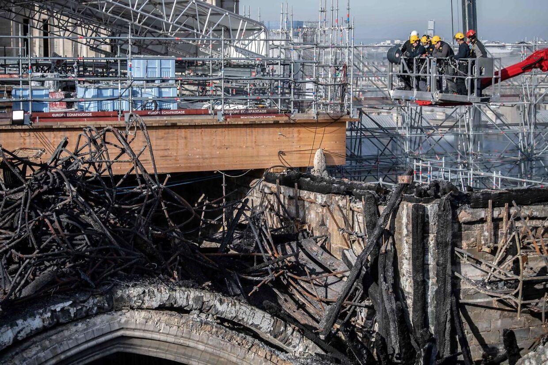 Arbejdere på en kran ser ned på de udbrændte dele af Notre Dame.