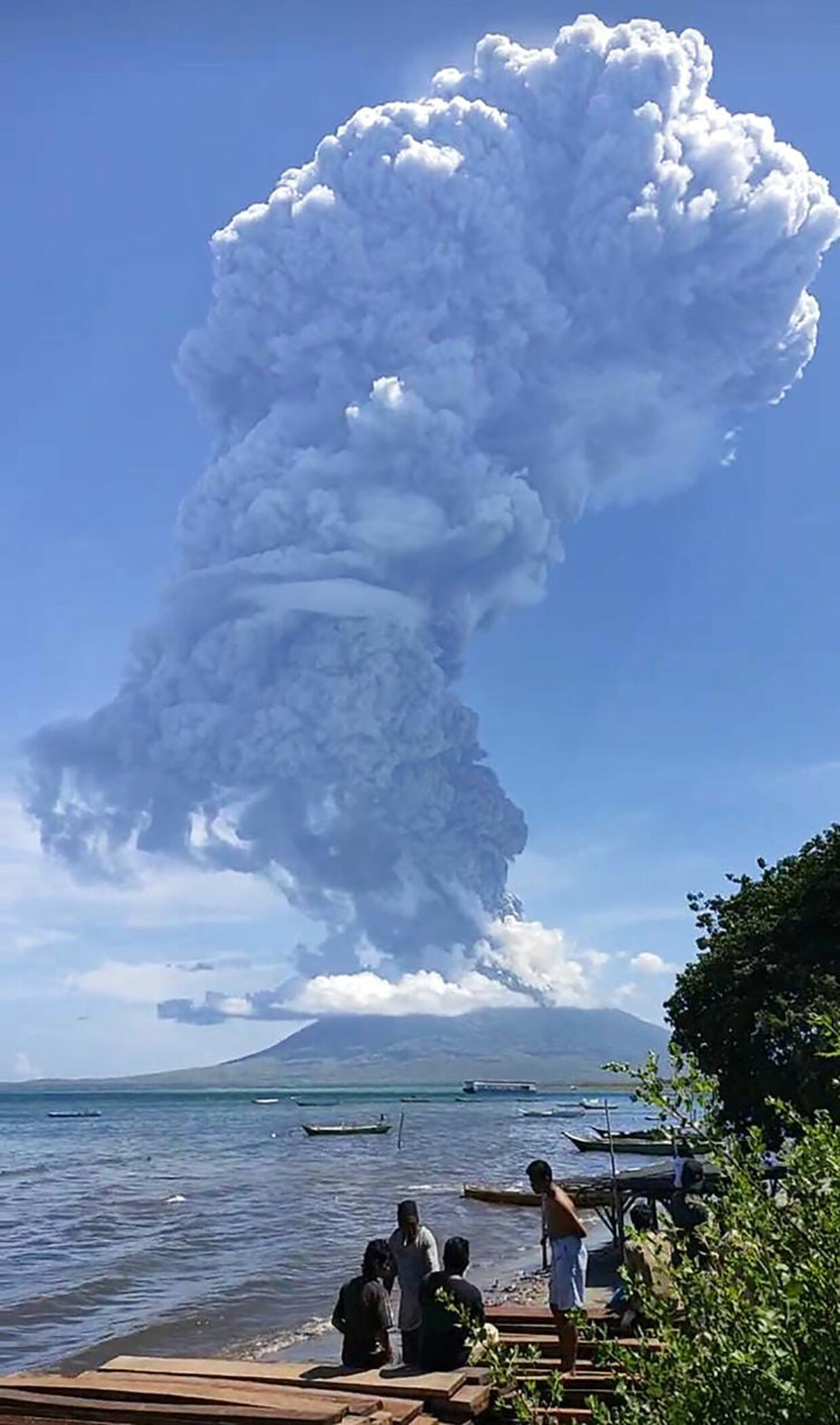 Residents gather to watch as Mount Ili Lewotolok spews ash during a volcanic eruption in Lembata, East Nusa Tenggara on November 29, 2020. (Photo by JOY CHRISTIAN / AFP)