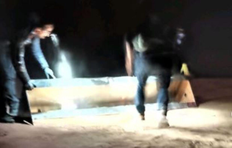 De fire mænd er i færd med at fjerne metal-monolitten.