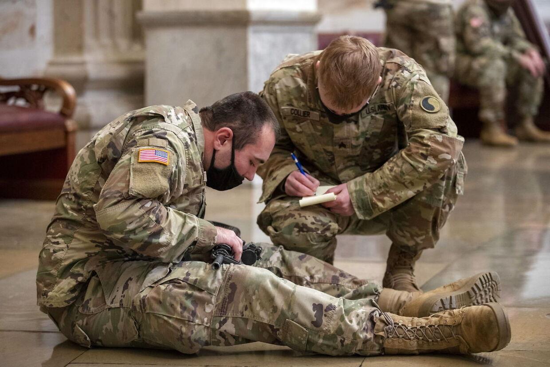 En soldal fra Nationalgarden skriver serienummeret på sit våben ned.