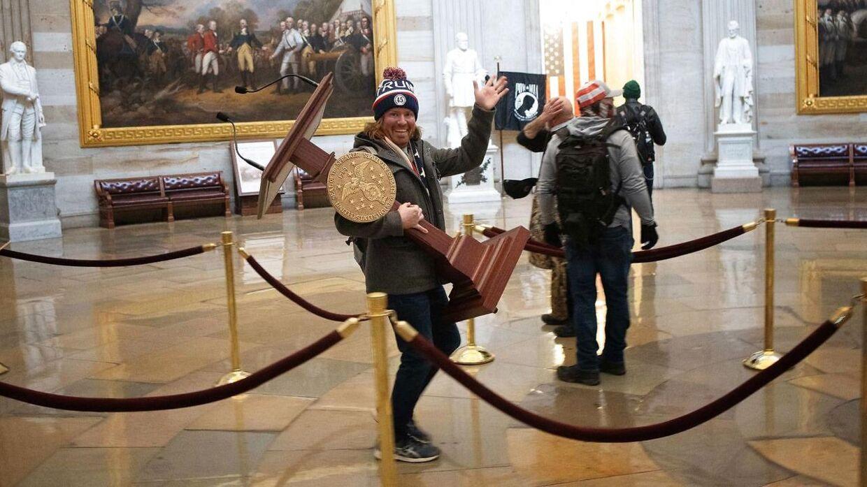 Billedet af Adam Johnson, som storsmilende og uhindret bar talerstolen ud af kongressen er gået verden rundt, og skal tjene som bevismateriale mod ham i den kommende retssag. (Foto: Scanpix)